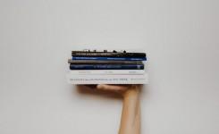 hand met boekenstapel